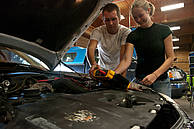 Male and female student work under car hood
