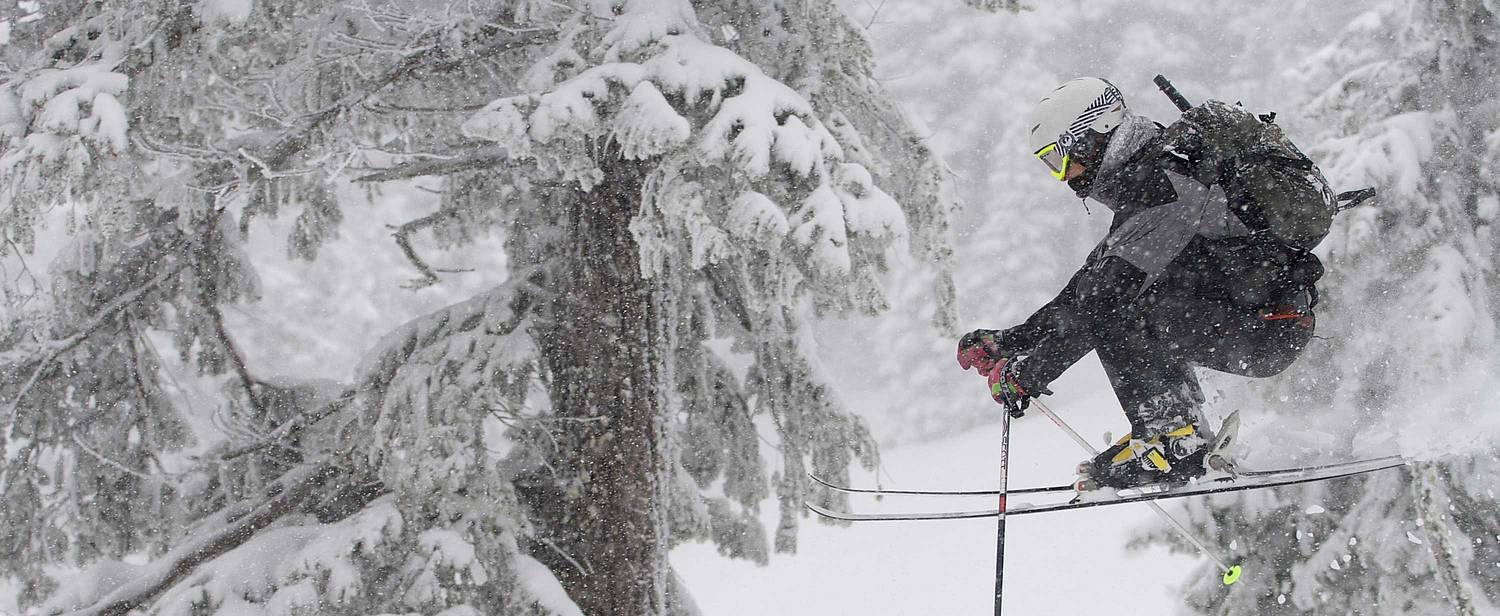 WWU student swoops down a snowy mountain on a snowboard.