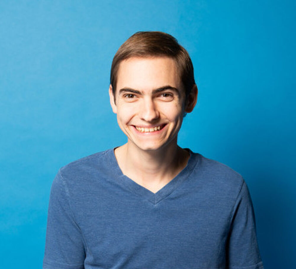young man in a blue shirt smiling against a blue background.