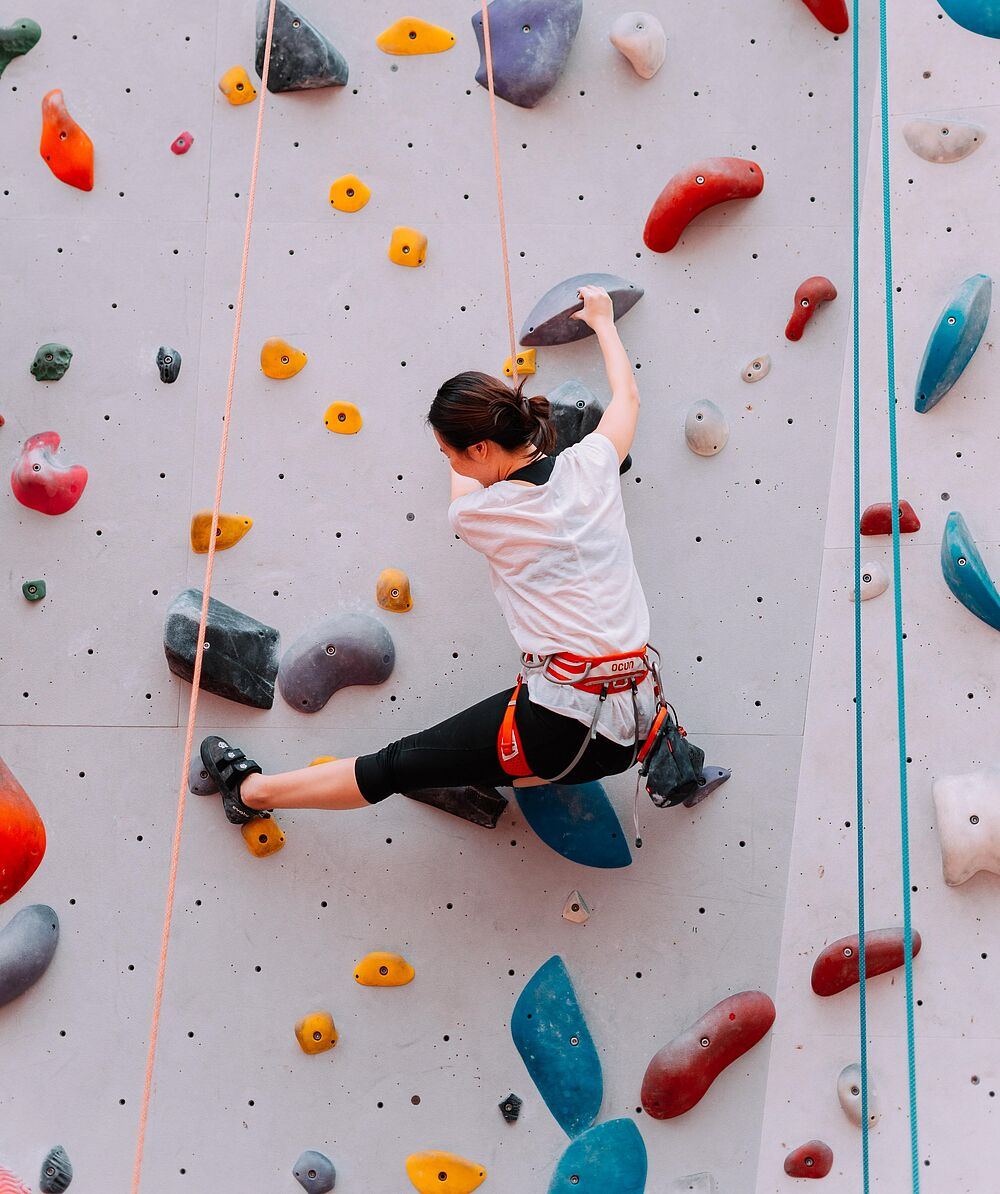 Climber climbing an indoor climbing wall full of colorful holds.