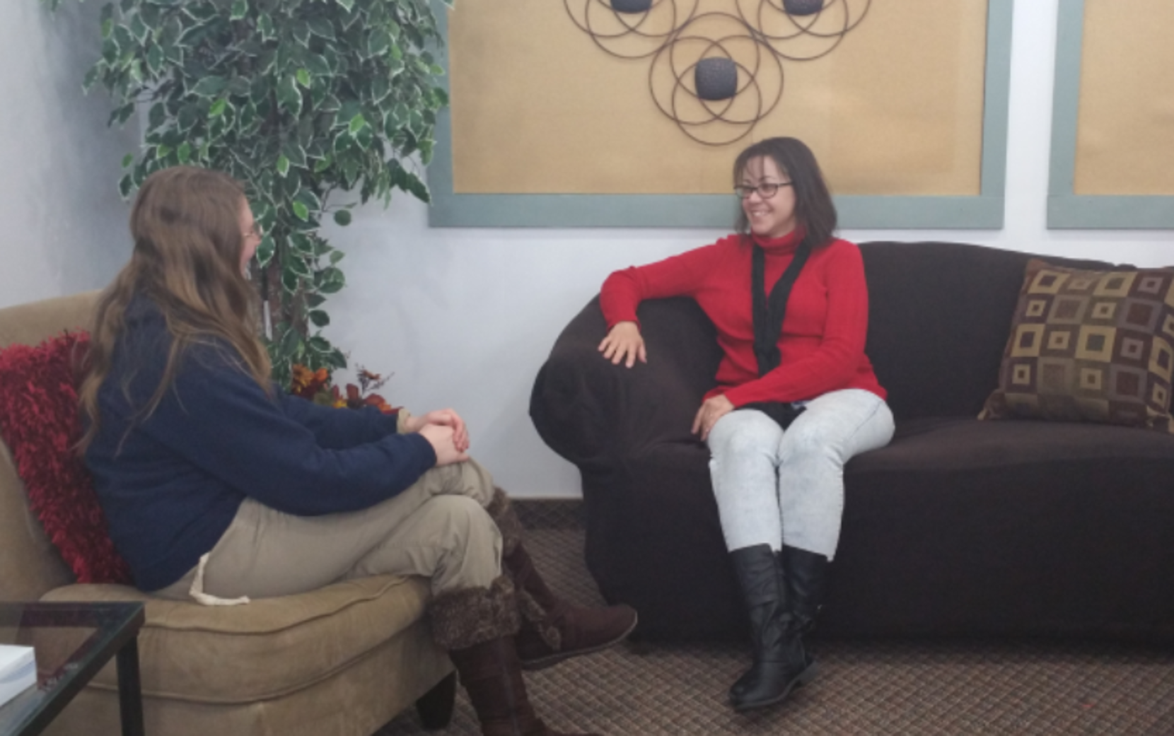 A MSW student and a professor sit across from each other in the therapy space.