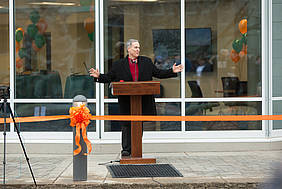President John McVay stands behind the uncut orange ribbon, giving a speech at the ribbon cutting for Bower's Hall.