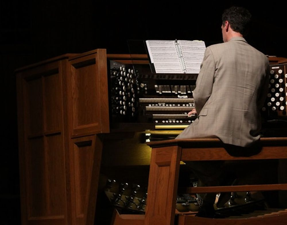 man in a gray suit at an organ in low light