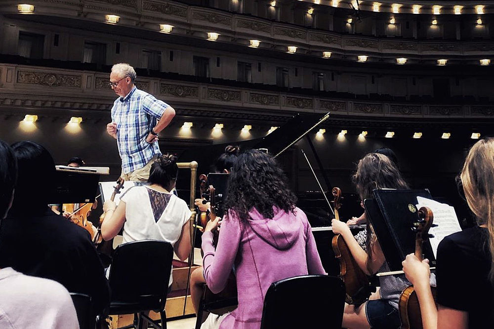 Brandon Beck conducts the students' rehearsal before the performance in Carnegie Hall