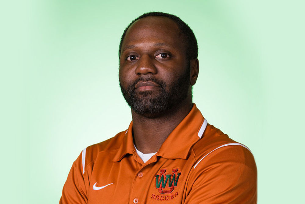 Coach William Burns stands in an orange WWU athletics polo against a green background.
