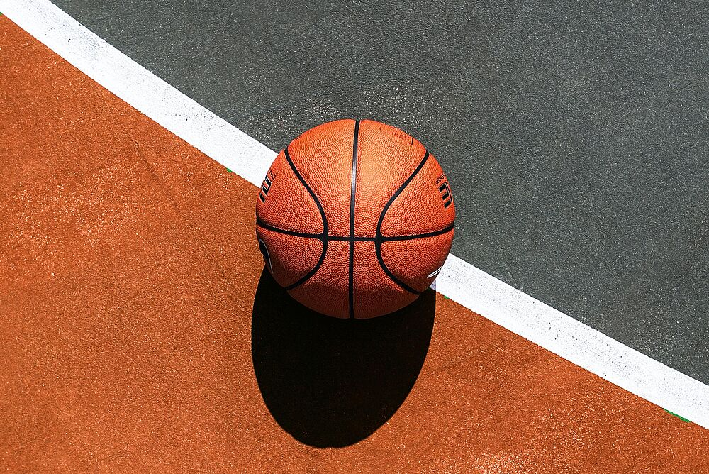 basketball on a green and orange basketball court with while lines