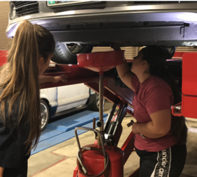 Bouit (left) shows Kelsey Duran, senior social work major, how to change the oil in her car.