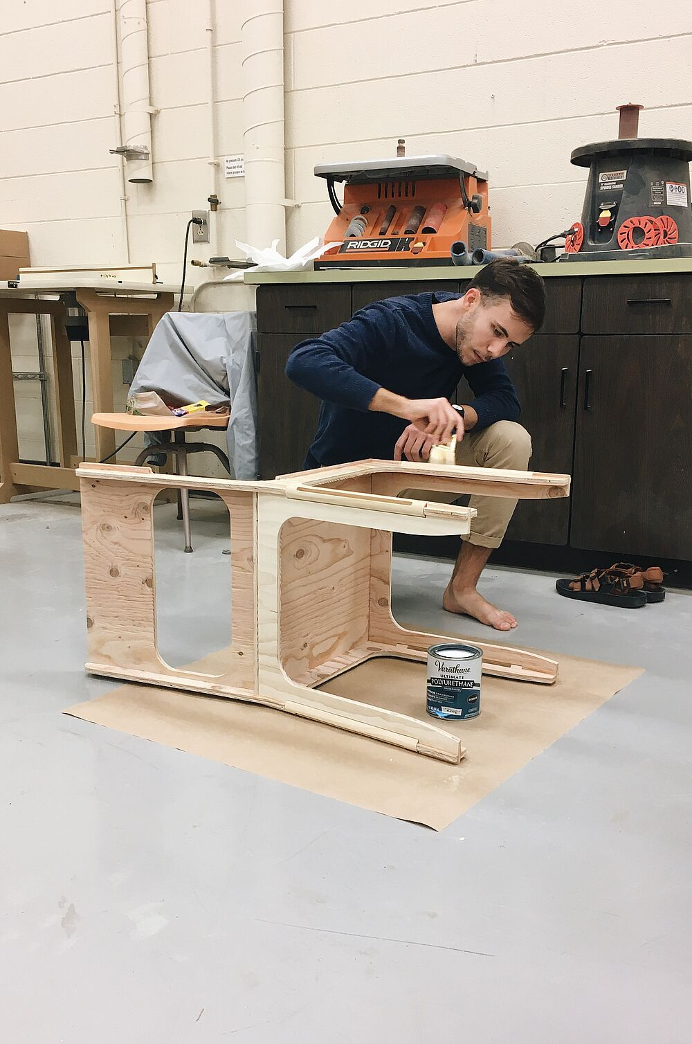 Logan Seibold works on building his chair in the product design work room.