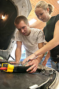 Students use diagnostic screen under car hood