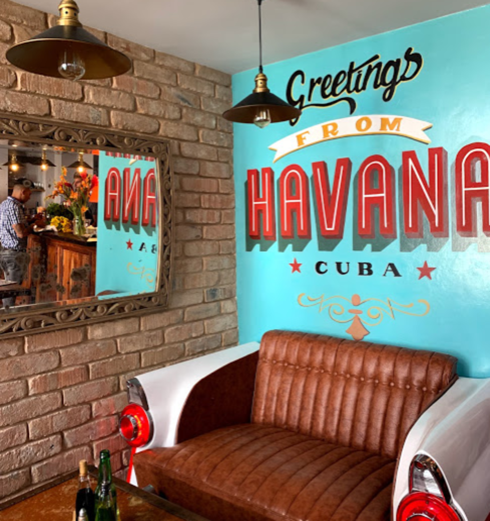 "blue wall with ""Havana"" written on it.  A leather bench stands below the room's wall."