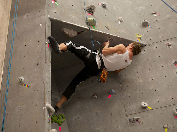 A student reaches for a lengthy hold bolted to the indoor climbing wall.