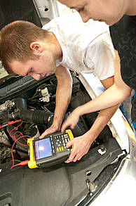 Students press buttons on diagnostic computer under car hood