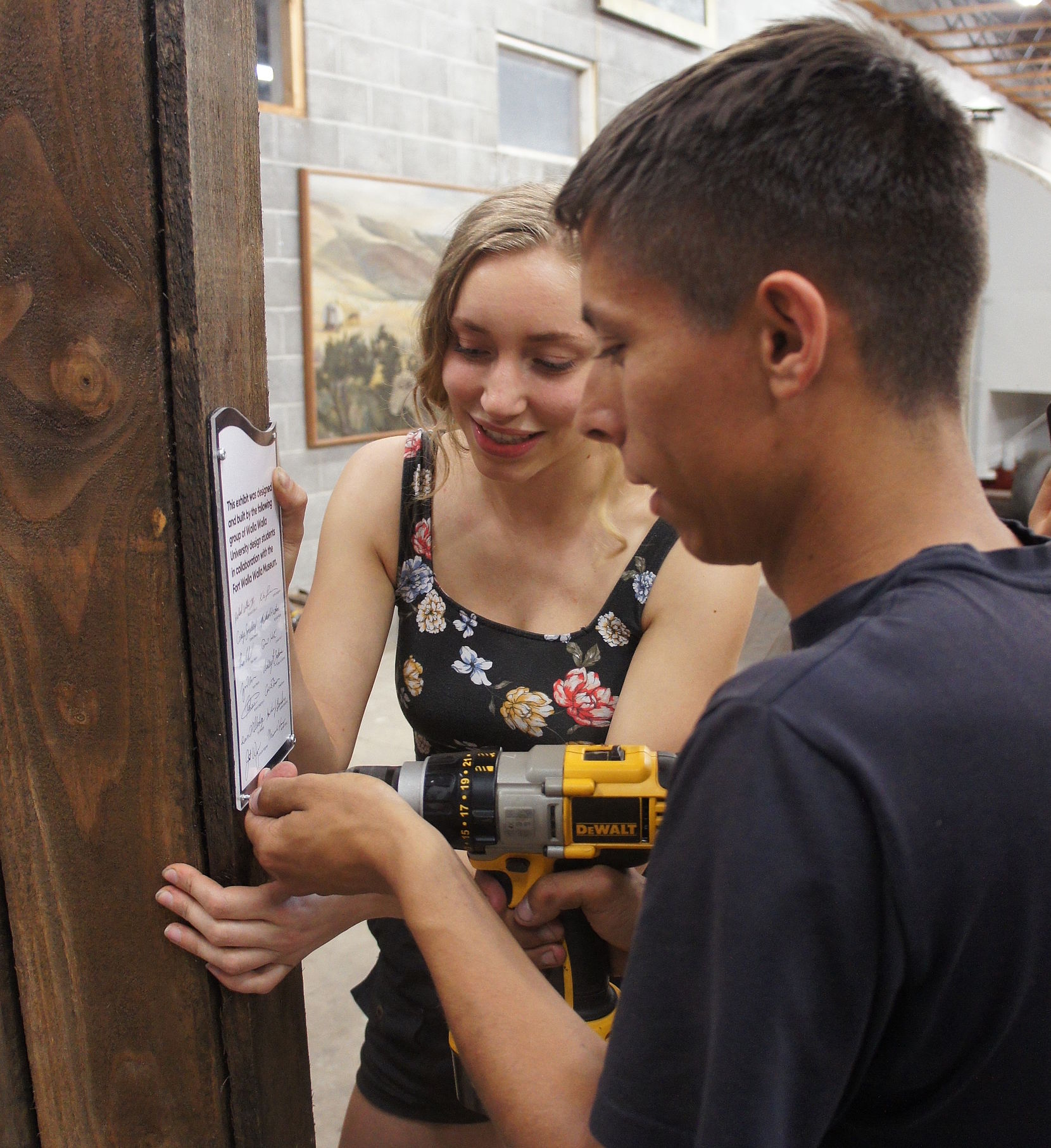 Student uses a screwdriver to install a sign on the new exhibit while another student holds the sign.