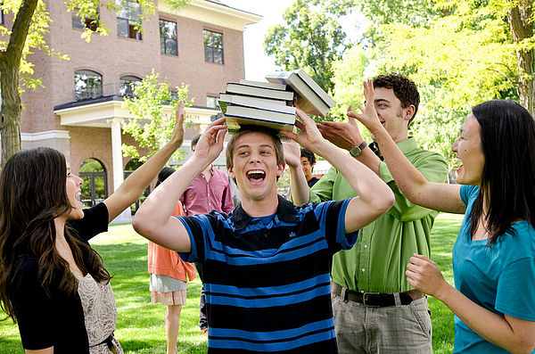A group of students stand around another outside of the Admin building while he tries to balance textbooks on top of his head.