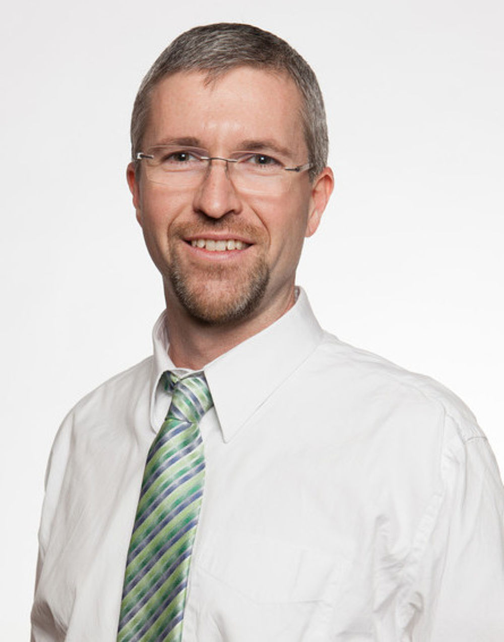 Professional portrait of David Lindstrom wearing a white shirt and striped green/blue tie.