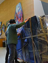 Movers with Bekins Northwest bring a newly acquired grand piano into the Fine Arts Center.