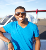 A student pilot leans on his aircraft.