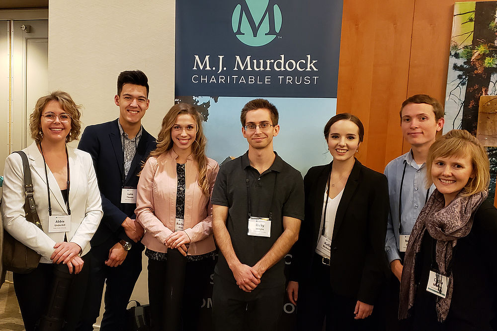 Six students and CJ Brothers stand in formal clothing in front of a banner for the M.J. Murdock Charitable Trust
