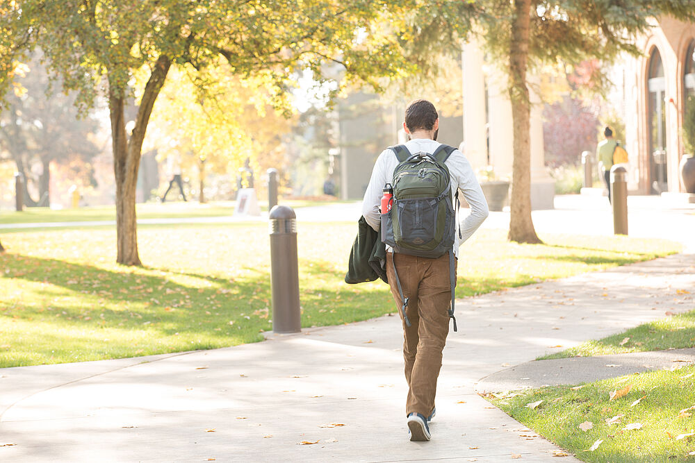 Student walking on a sidewalk wearing a backpack