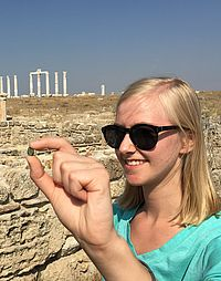 Bumgardner, senior sociology major, holds the Byzantine coin before handing it over to archaeologists.