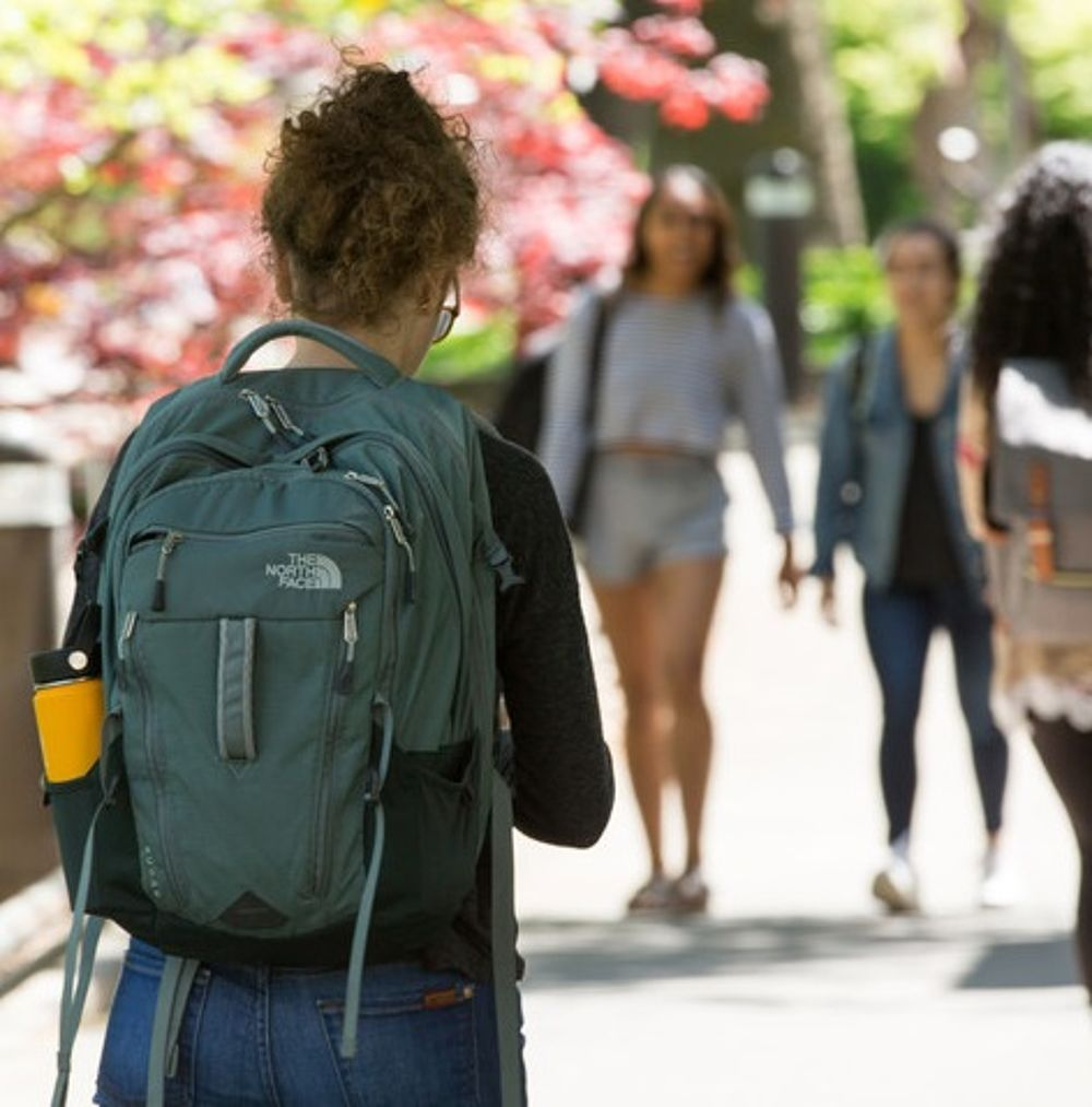 Students with backpacks walking along sidewalk