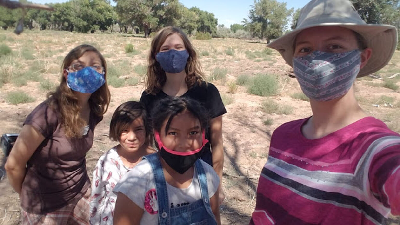 A group photo of five girls in masks.
