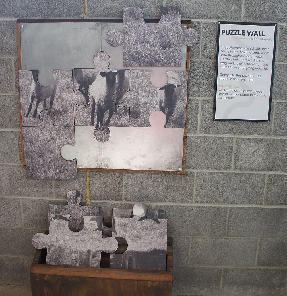A display of large puzzle pieces of a picture of sheep hangs on the wall.