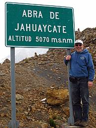 Man posing by mountain pass road sign