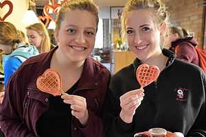 Two girls with heart shaped waffles at residence hall Valentine's day celebration