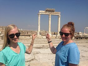 Sara Bumgardner and Sarah Thompson pose in the ruins of Laodicea with the coins they found.