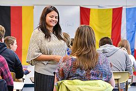 Spanish professor Alma Alfaro stops to talk with a student in the classroom with other Spanish students as well as flags from Spanish-speaking countries surrounding her.
