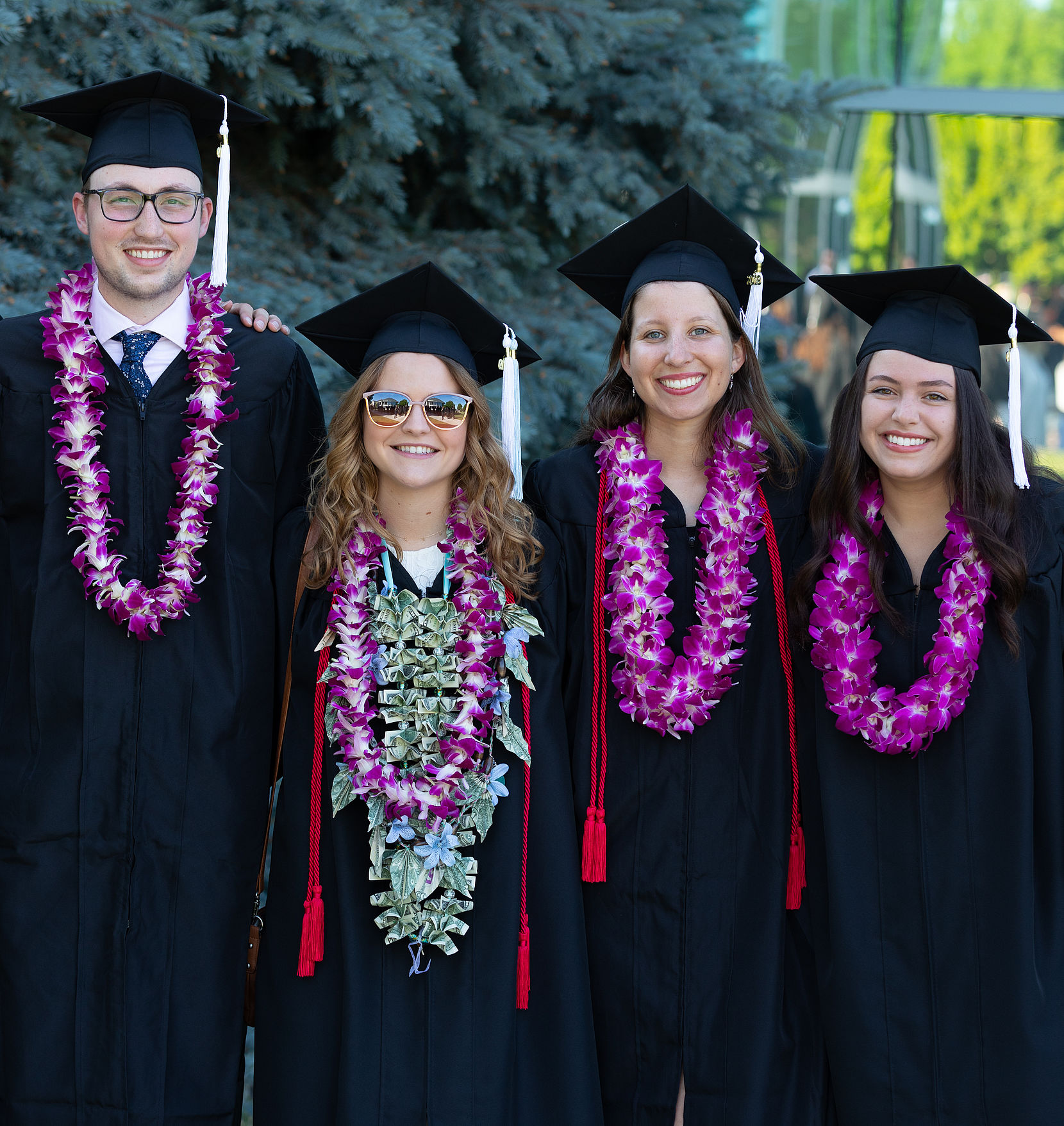 Four graduates in caps and gowns pose in a row, one man and three women.