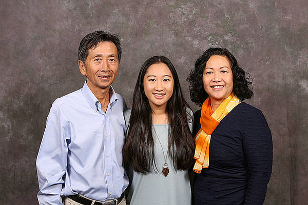 A family of three poses for a professional photograph during Family Weekend.
