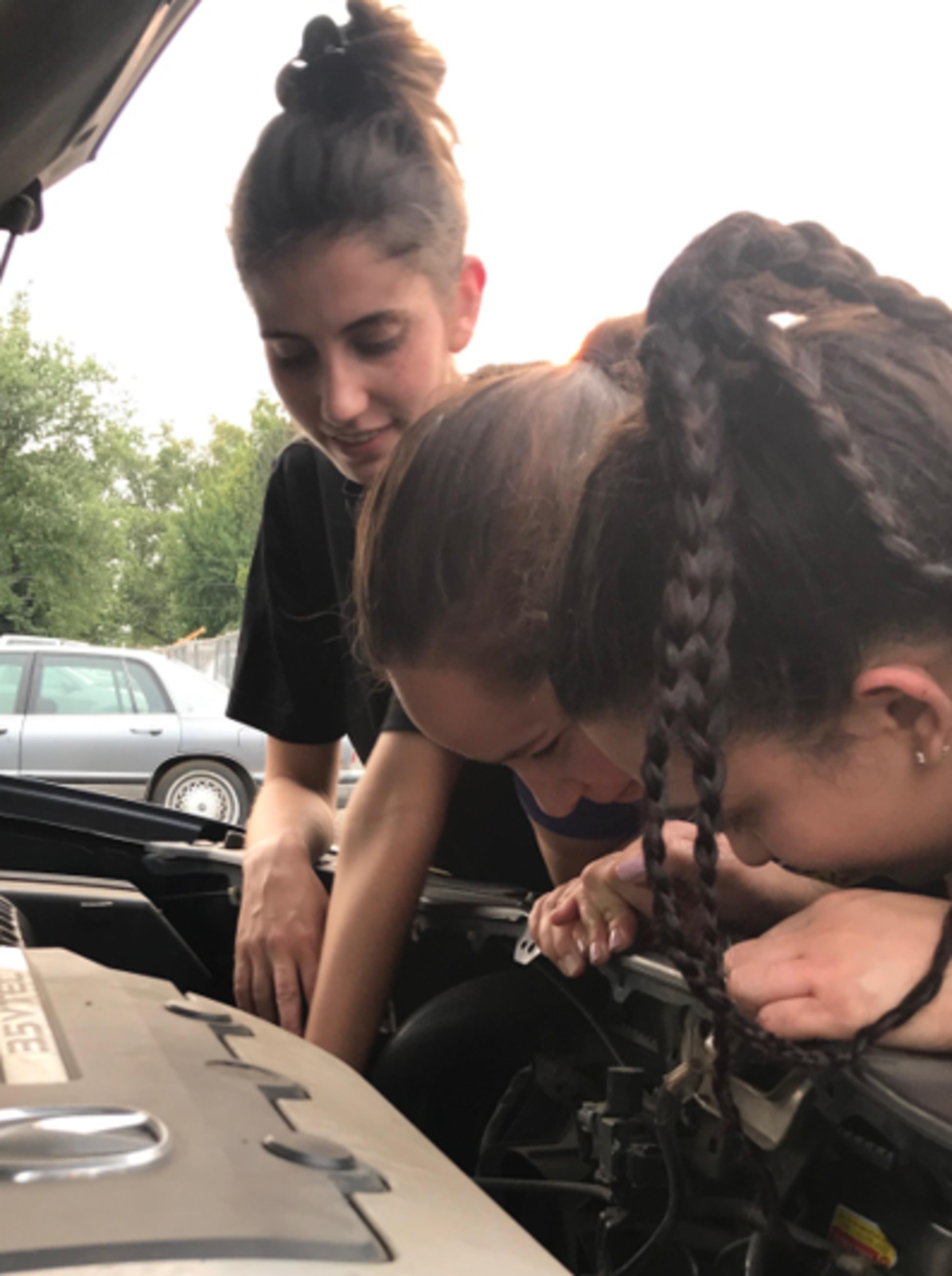 Bouit leans under a car hood with students to point out engine specifics.