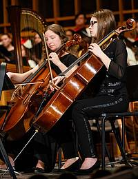 Two students play chellos in the orchestra.