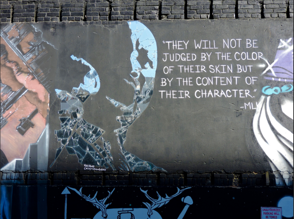Mural on a brick wall of MLK with a quote painted nearby