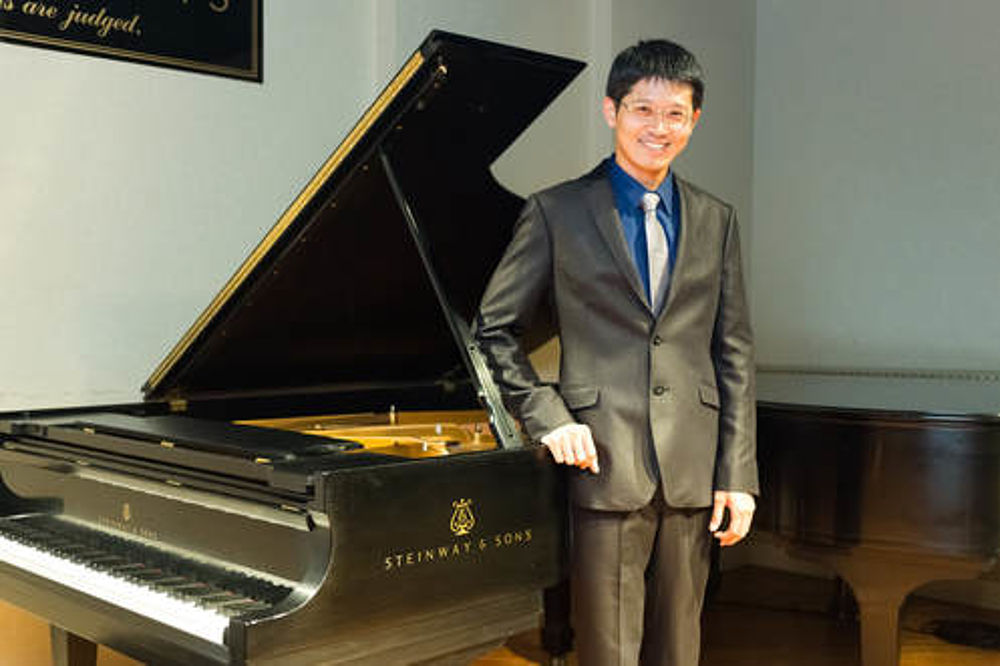 Asian man in a suit standing beside an open grand piano