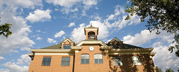 The dark brown brick of the Administration Building contrasts against the bright blue sky full of white clouds.