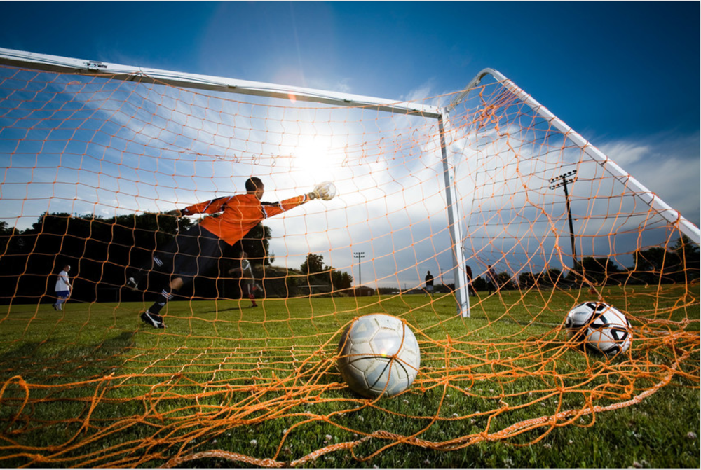 soccer goal against dramatic sky with goalie reaching for the ball