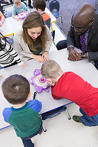 Sebastien and Robinson sit with two preschoolers and play a game