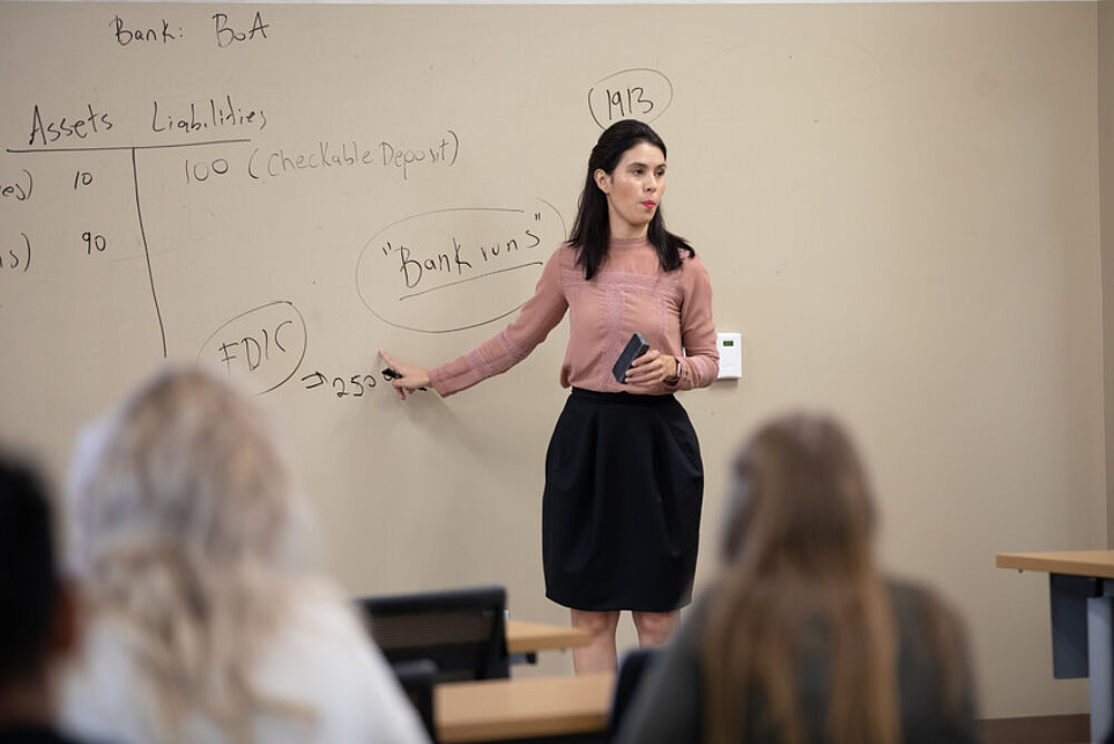 Business professor teaches in front of a white board