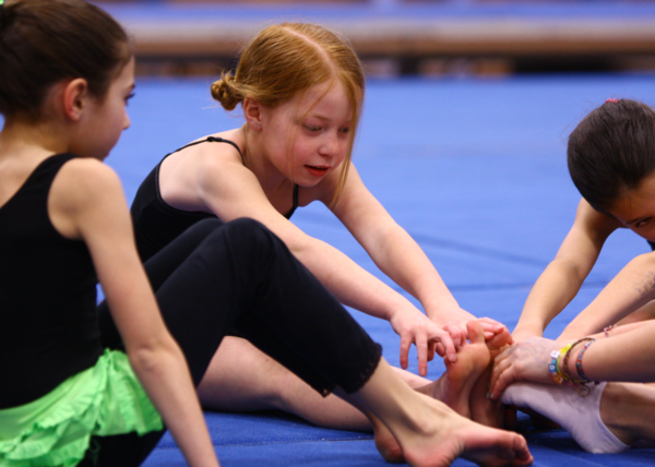 Young gymnast reaches for her toes during a kidnastics class.