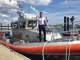 Welch stands on the bow of a 45-foot Response Boat-Medium at Coast Guard Station New London in Connecticut.