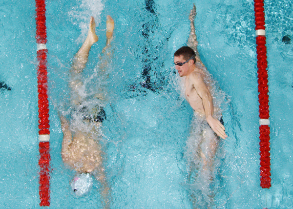 Two swimmers pass each other during lap swim.