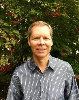 Portrait picture of Bryan Clay standing in front of a floral bush. Clay is a an active member of the University Board, a position he has held since 2016.